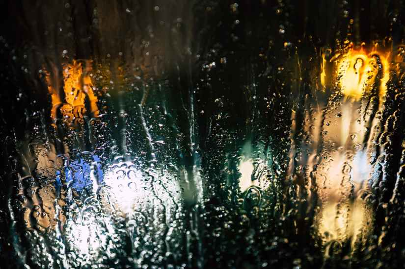 selective photography of glass window with drops of water during nighttime